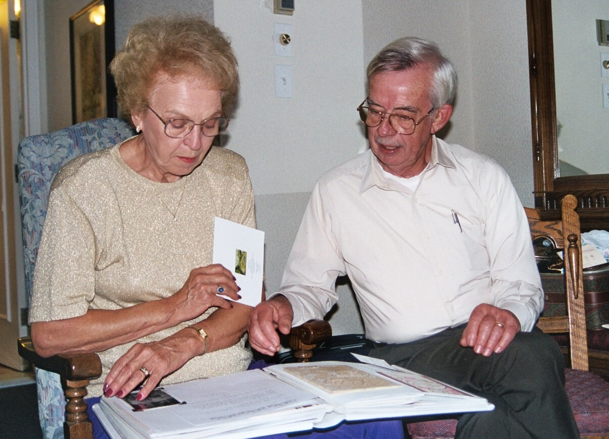 Mom and Dad enjoy an album of letters and cards from friends who wrote to congratulate them.
