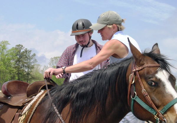 A therapeutic riding assistant helps Matt get ready to ride.  Near Williamsburg, Virginia, April 2005.