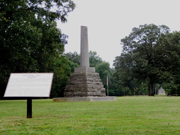 This monument marks the burial site of Meriwether Lewis. The ruins of the Grinder house are visible on the ground adjacent to the visitor's center, far right. Natchez Trace Parkway, Lewis County, Tennessee, September 18, 2014