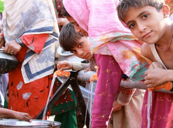 Children collect clean water provided by UKAid.  Image via Wikimedia Commons