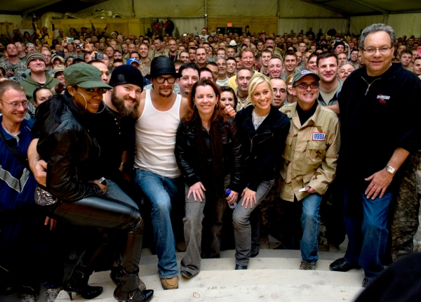 2008 USO Holiday Tour in Kandahar, Afghanistan.  Celebrities bring music and entertainment to service members and their families stationed overseas. DoD photo by Mass Communication Specialist 1st Class Chad J. McNeeley; image in the public domain.
