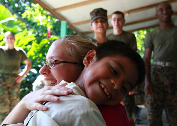 The NGO Give a Kid a Backpack brings smiles in 2010. Via Wikimedia Commons  Public domain photograph from defenseimagery.mil