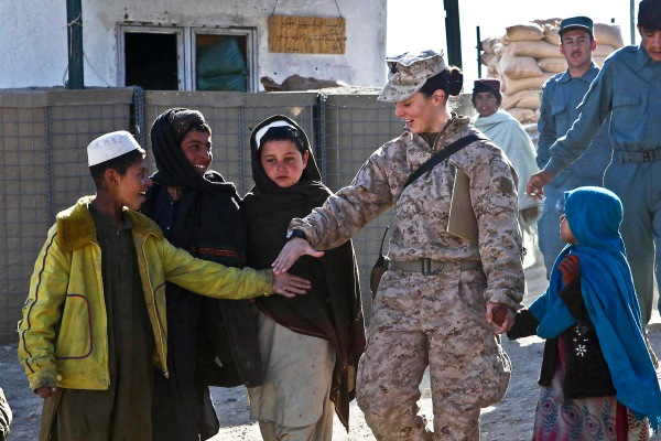 Petty Officer 2nd Class Kimberley Ryan holds hands with Afghan children as they walk to the local children's shura in Afghanistan's Helmand province, 2012. Photo by Cpl. Ed Galo, U.S. Marine Corps, public domain via Wikimedia Commons